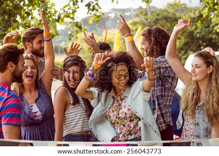 Happy hipsters dancing to the music at a music festival - stock photo