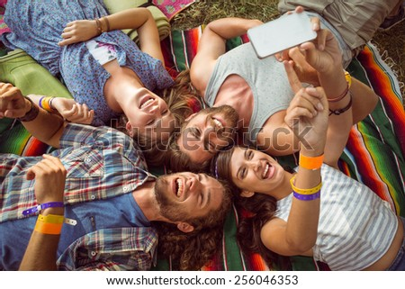 Happy hipsters lying on the grass at a music festival - stock photo