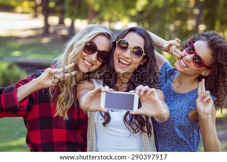 Happy hipsters taking a selfie in the park on a sunny day - stock photo