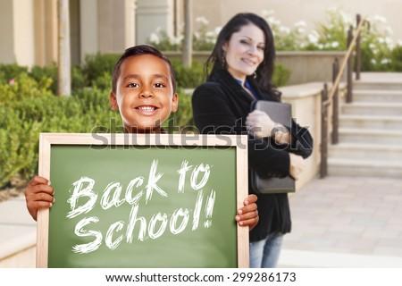 Happy Hispanic Boy Holding Back to School Chalk Board Outside on School Campus as Teacher Looks On. - stock photo