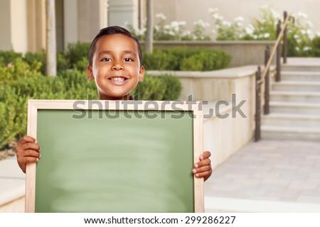 Happy Hispanic Boy Holding Blank Chalk Board on School Campus. - stock photo