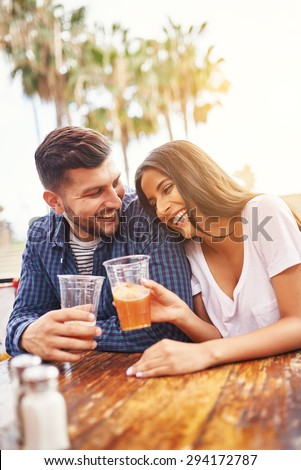 happy hispanic couple drinking beer in outdoor pub with lens flare - stock photo