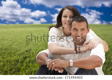Happy Hispanic Couple Sitting in Grass Field. - stock photo