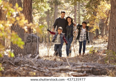 Happy Hispanic family with two children walking in a forest - stock photo