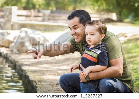 Happy Hispanic Father Points with Mixed Race Son at the Park Pond. - stock photo