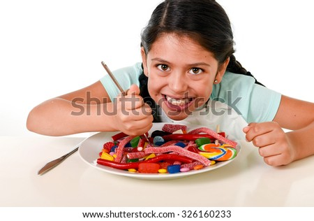 happy hispanic female child eating dish full of candy and gummies with fork and knife  in sugar excess and sweet nutrition abuse isolated on white background - stock photo