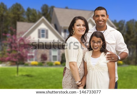 Happy Hispanic Mother, Father and Daughter in Front of Their Home. - stock photo