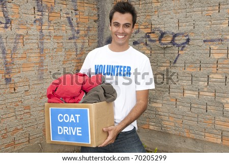 happy hispanic volunteer with coat drive donation box - stock photo