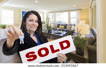 Happy Hispanic Woman with House Keys and Sold Sign in Beautiful Living Room. - stock photo