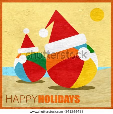 Happy Holidays greeting with beach balls wearing Santa hats on wood grain texture - stock photo