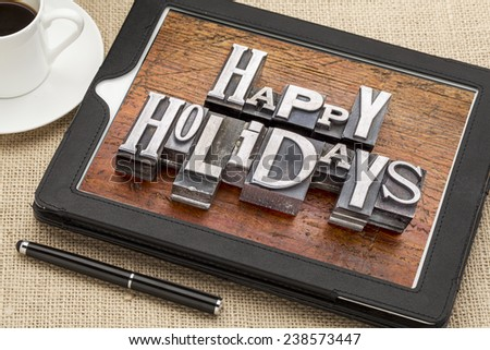 Happy Holidays greetings  in vintage metal type printing blocks on a digital tablet with a cup of coffee - stock photo