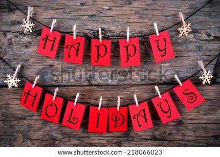 Happy Holidays Greetings on red Tags Hanging on a Line with Snowflakes, Christmas or Winter Background - stock photo