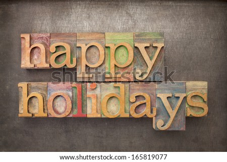 happy holidays - text in letterpress wood type against grunge metal background - stock photo