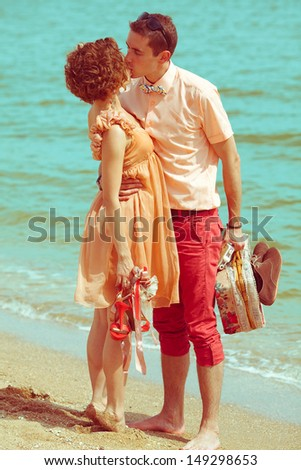 Happy honeymoon concept. Young married couple of hipsters standing together on the beach, kissing, holding their photocamera, suitcase and shoes. Sunny summer day. Vintage style. Outdoor shot - stock photo