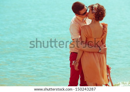 Happy honeymoon (vacation) concept. Young happy married hipsters in trendy clothes standing and kissing over blue ocean (sea) background. Sunny summer day. Copy-space. Outdoor shot - stock photo