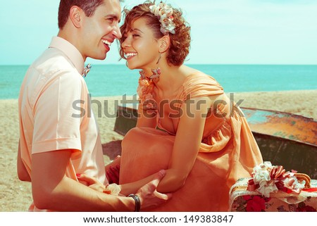 Happy honeymoon (vacation) concept. Young married couple of hipsters in trendy clothes playing and laughing on the beach. Sunny summer day. Copy-space. Outdoor shot - stock photo