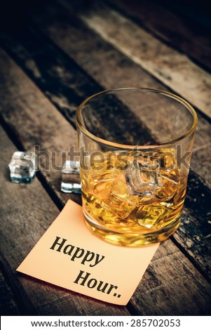 happy hour with label on paper note. Glass of scotch whiskey  - stock photo