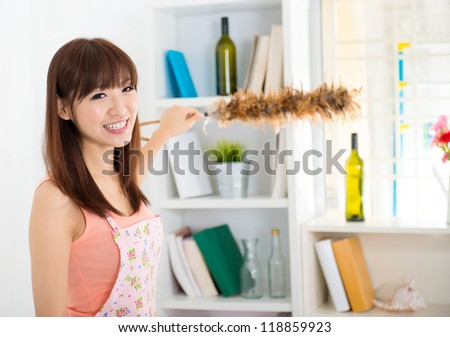 Happy housewife cleaning house with duster - stock photo