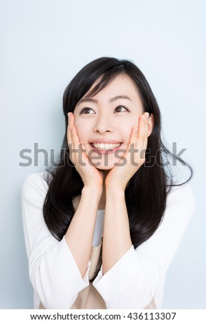 Happy housewife with apron sing against light blue background - stock photo