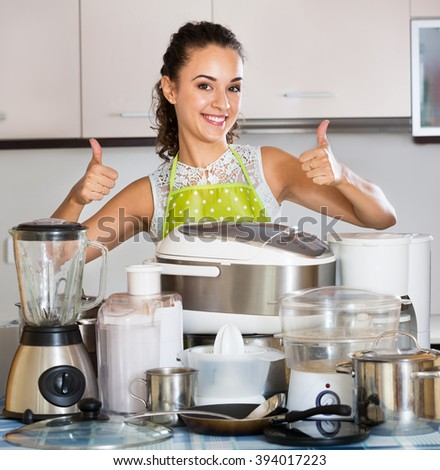 Happy housewife with the kitchen appliances at a home  - stock photo