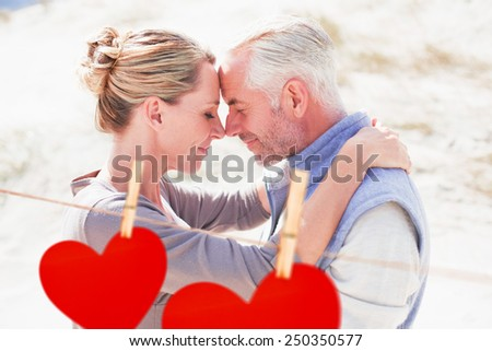 Happy hugging couple on the beach looking at each other against hearts hanging on a line - stock photo