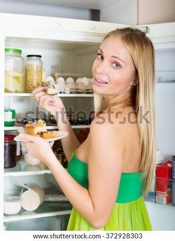 Happy hungry woman near opening fridge eating cake in her kitchen