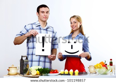 Happy husband and wife cooking together at home - stock photo