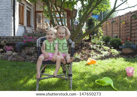 happy identical twin sisters at home in the garden, playing and having fun on a chair - stock photo