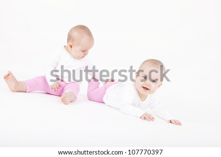 happy identical twin sisters playing on the ground - stock photo
