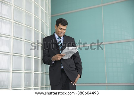 Happy Indian businessman looking down and reading a newspaper. - stock photo
