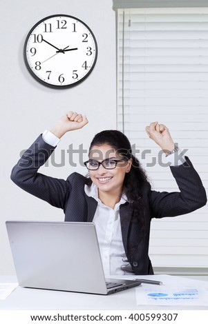 Happy Indian businesswoman raises hands up in the office with a laptop on desk, celebrating her success - stock photo