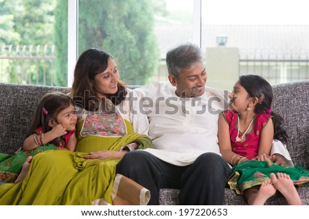 Happy Indian family at home. Asian parents chit chatting with their kids, sitting on sofa. Parents and children indoor lifestyle. - stock photo