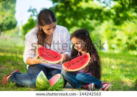 Happy indian family eating watermelon in park - stock photo
