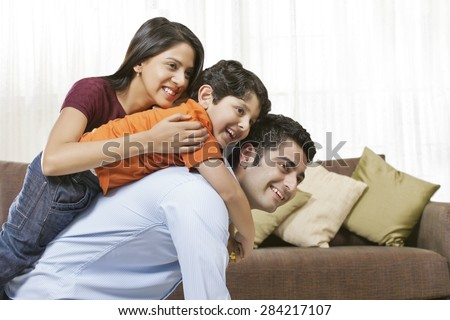 Happy Indian family of three at home - stock photo