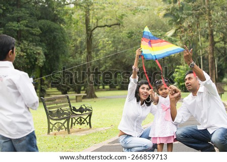 happy indian family playing kite in the park - stock photo