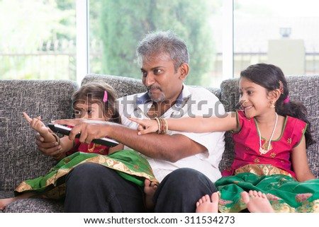 Happy Indian family watching tv together, switching channel with remote control, father and children indoor living lifestyle at home. - stock photo