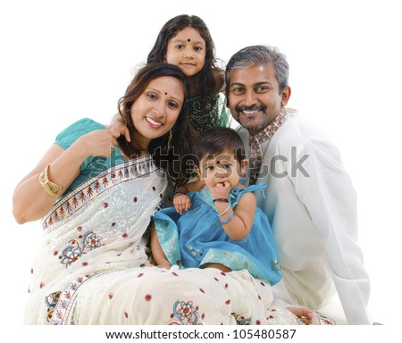 Happy Indian family with two children in traditional costume sitting on white background - stock photo