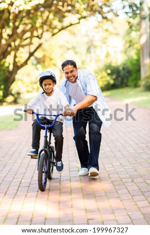 happy indian father teaching his son to ride a bicycle at the park - stock photo