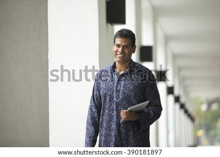 Happy indian man outdoors. portrait of an indian man wearing a Traditional kurta. - stock photo