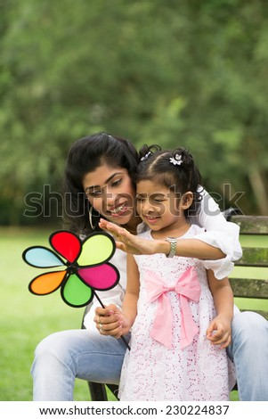 Happy Indian mother and daughter playing in the park. Lifestyle image.  - stock photo