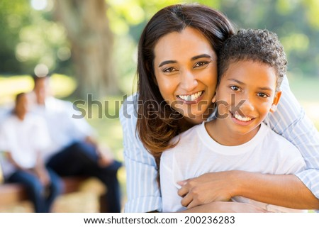 happy indian mother hugging her son in front of family outdoors - stock photo