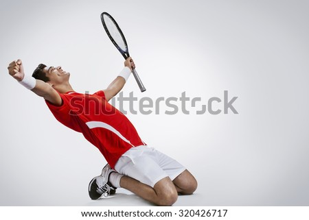 Happy Indian tennis player celebrating success over gray background - stock photo