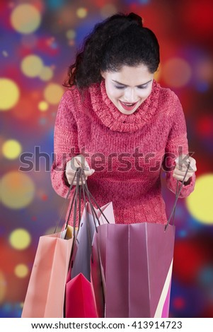 Happy indian woman wearing winter clothes and opens shopping bags with christmas background - stock photo