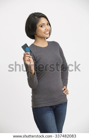 Happy Indian young girl showing credit card on white. - stock photo