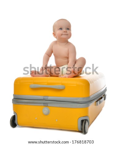 Happy infant baby toddler sitting on yellow plastic travel suitcase on wheels getting ready for vacation and looking at the corner isolated on a white background - stock photo