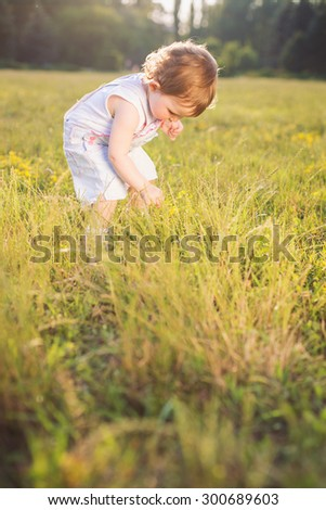 happy infant girl is standing in the grass. - stock photo