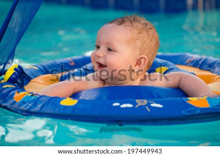 Happy infant playing in pool while sitting in baby float with canopy - stock photo