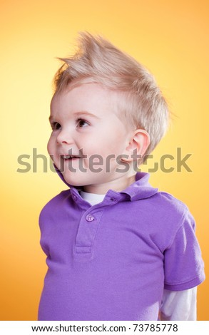 Happy interested little boy in violet looking up - stock photo