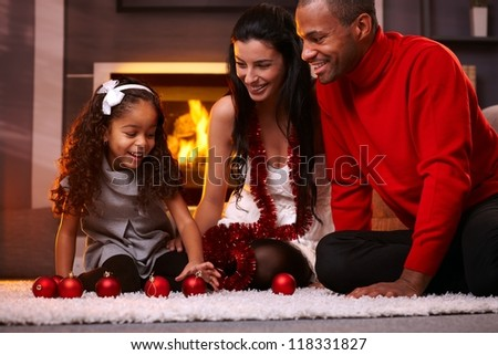 Happy interracial family having fun at home at christmas time, being together, sitting on floor, playing with christmas balls smiling. - stock photo