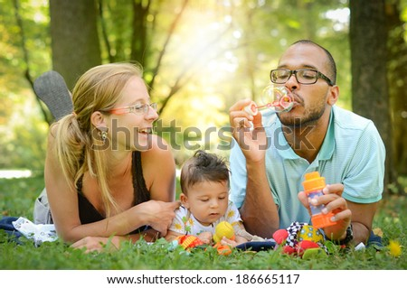 Happy interracial family is blowing bubbles. Happy interracial family is enjoying a day in the park. Mother father and mulatto son are smiling and are picnicking in the green park. - stock photo